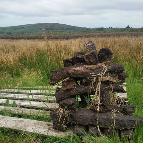 Stack of turf in Edenmore Bog with Cairn Hill in background in North Longford
